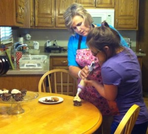 Helping decorate Salted Caramel Chocolate birthday cupcakes.  Recipe to come next week!